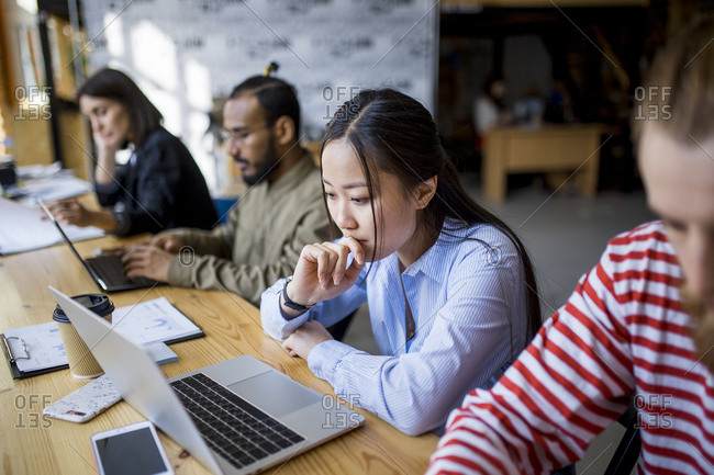 Young Asian woman concentrating on laptop screen while co-workers work