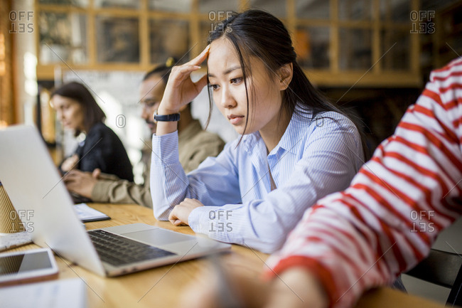 Young Asian woman reading on laptop screen sitting side by side with co-workers