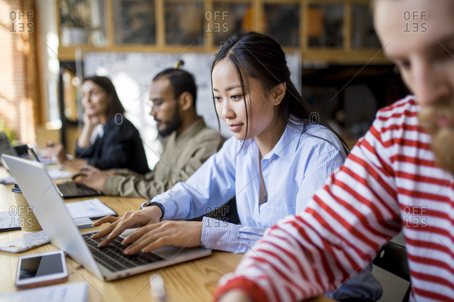 Asian woman working on laptop sitting side by side with multi ethnic co-workers