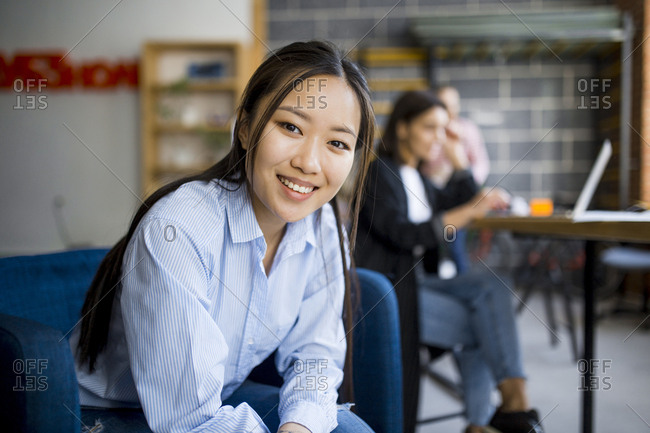 Portrait of young Asian female entrepreneur in co-working space