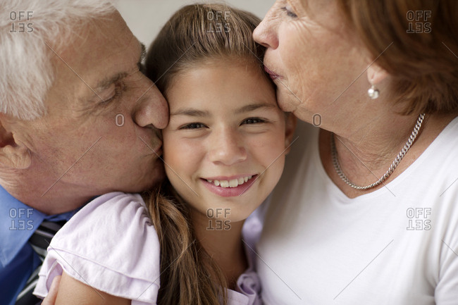 Senior couple kiss their granddaughter