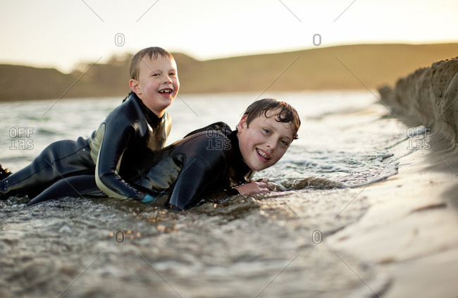 Boys lying in the sand at the beach in wetsuits