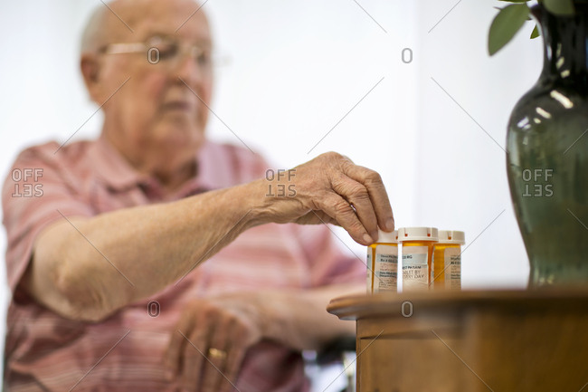 Senior man looking at several medicine bottles