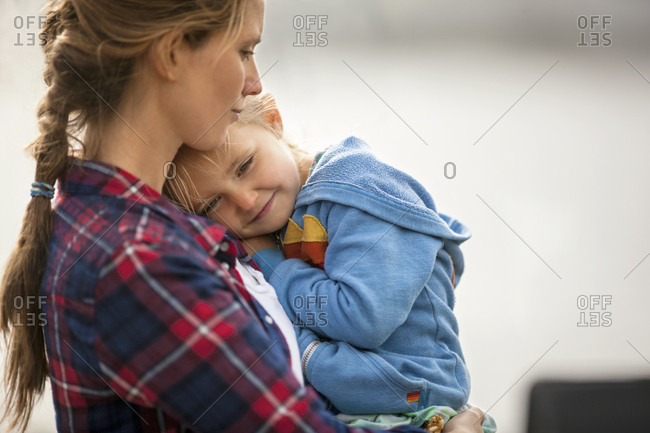 Smiling little girl snuggles happily in her mother's arms