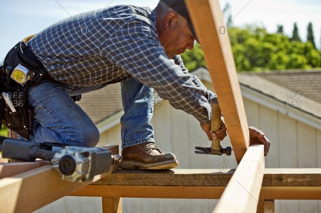 Builder taking measurements on a construction site