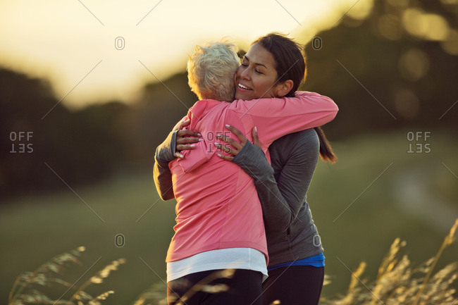 Smiling young woman embracing a mature friend before a run in the countryside