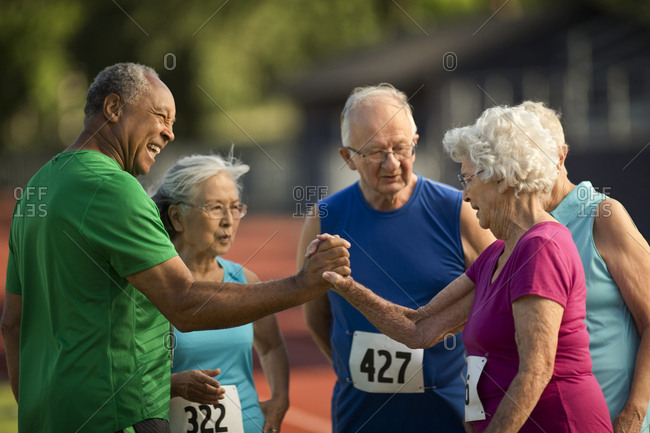 Happy seniors playfully challenge one another before an athletics event
