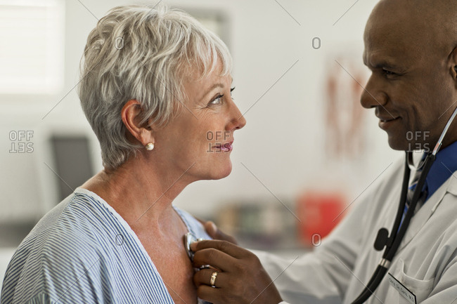 Mature woman gazes flirtatiously at the young doctor checking her heartbeat