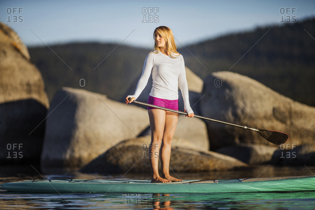 Young woman paddle boarding on a lake