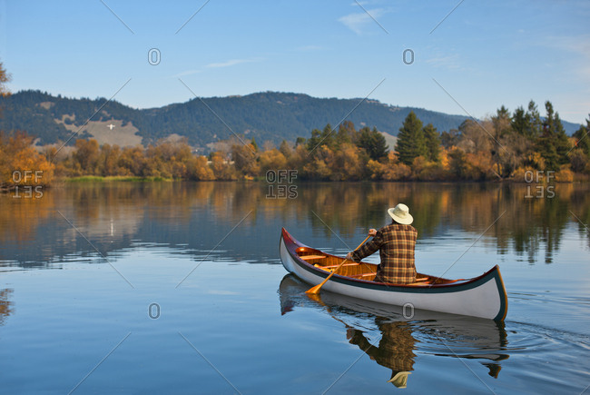 Man canoeing across a tranquil scenic lake