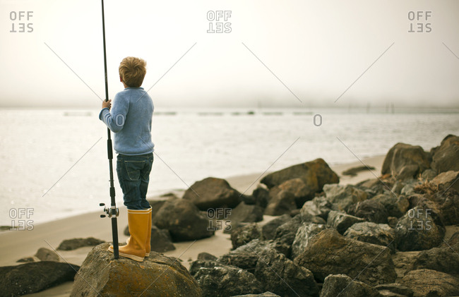 Young by standing on a rock holding a fishing rod