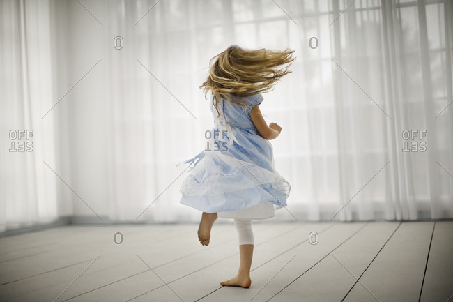 Little girl joyfully spinning around in bare feet in an empty room