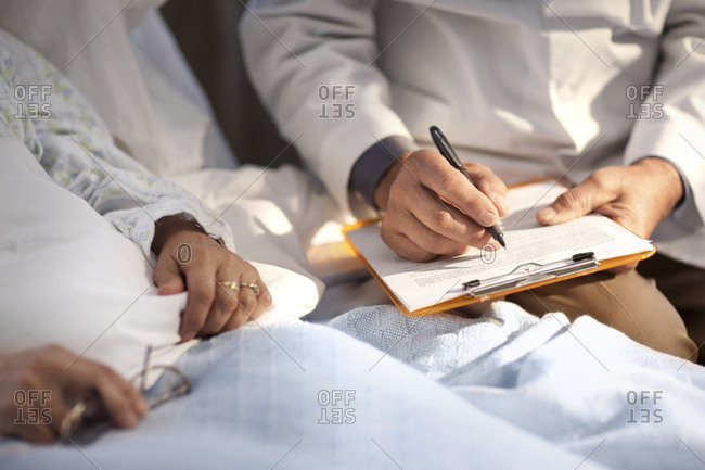 Doctor taking notes while sitting with a patient in hospital