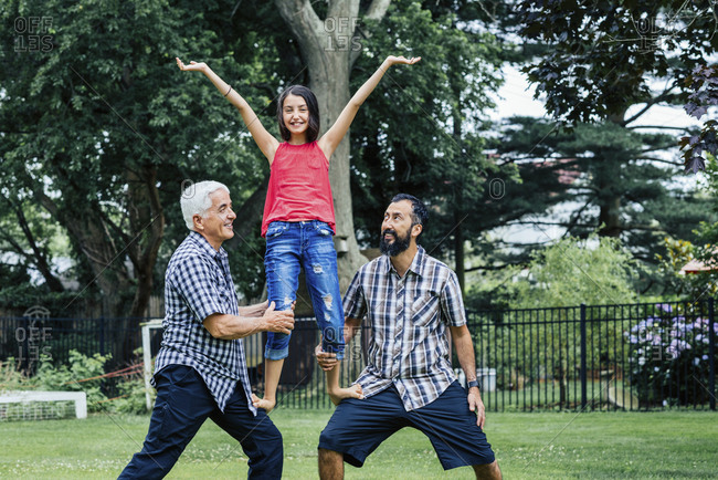 Portrait of girl standing on father's and grandfather's legs in yard