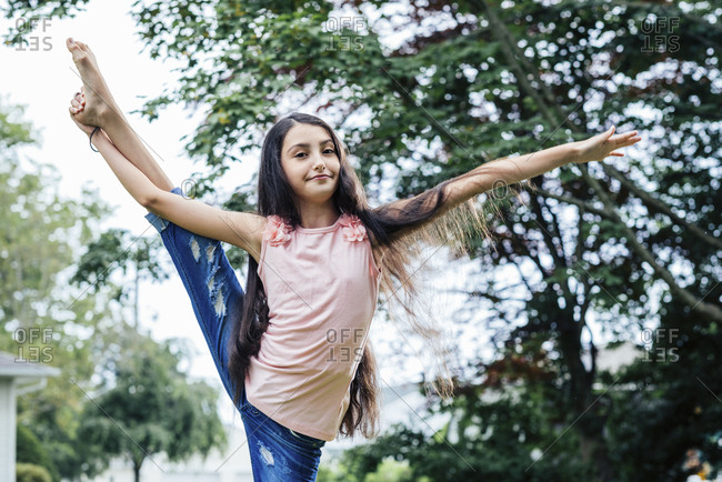 Portrait of confident girl doing stand split exercise in yard