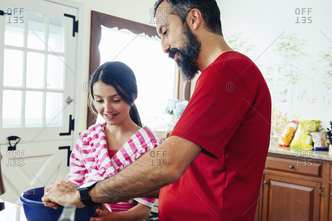 Smiling girl making pancakes with father in kitchen at home