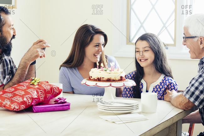 Happy family celebrating girl's birthday at table in house