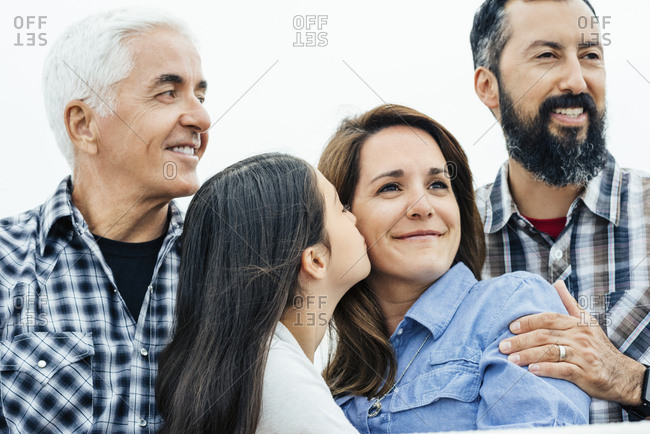 Loving girl kissing mother on cheek while standing with father and grandfather against sky