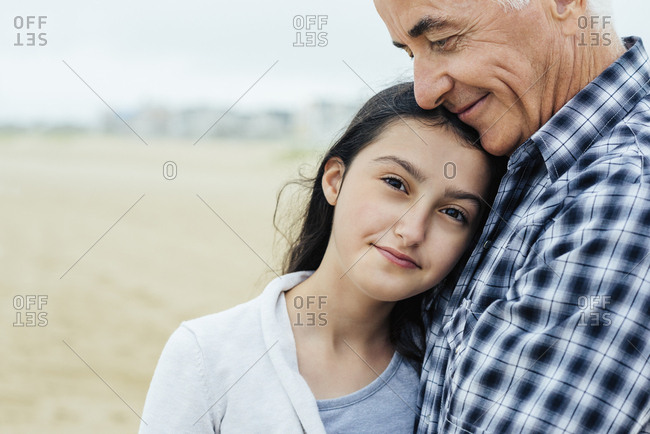 Portrait of girl embracing grandfather while standing at beach