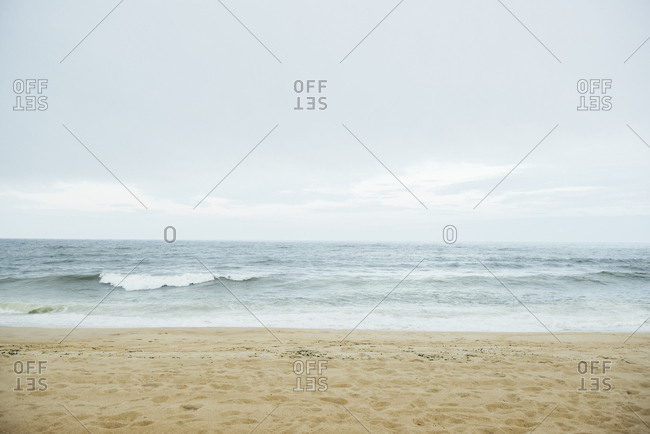 Scenic view of waves rushing in sea at beach against sky