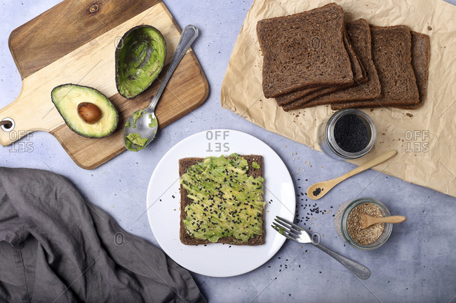 Top down view of toast spread with avocado and two types of sesame seeds