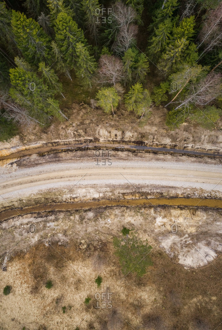 Abstract aerial view of empty dirt road next to forest, Estonia