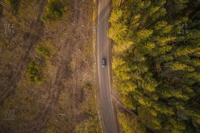 Aerial view of gray car on the road at sunset on the island of Vormsi, Estonia