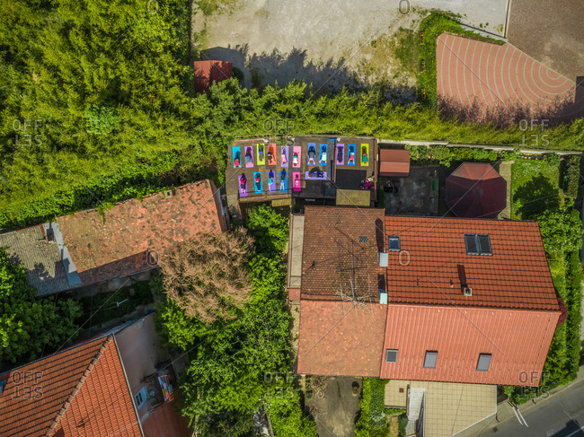 Aerial view of a group of people doing yoga on a terrace surrounded by trees in town