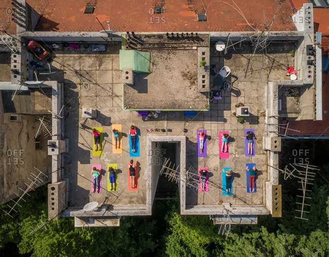 Aerial view of a group of people doing yoga on a rooftop in the city during a summer day