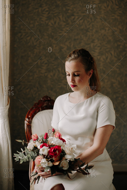 Bride sitting on chair and holding wedding bouquet