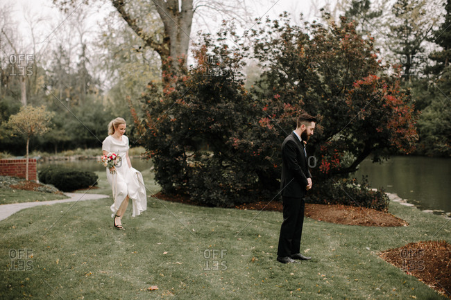 Bride walking towards groom with back turned to her