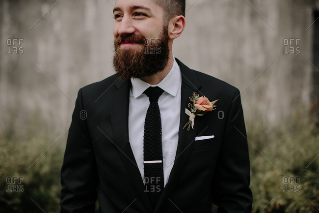 Portrait of a bearded smiling groom wearing a jacket with a boutonniere