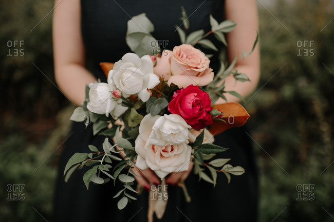 Bridesmaid holding bridal bouquet with red, white, and pink roses