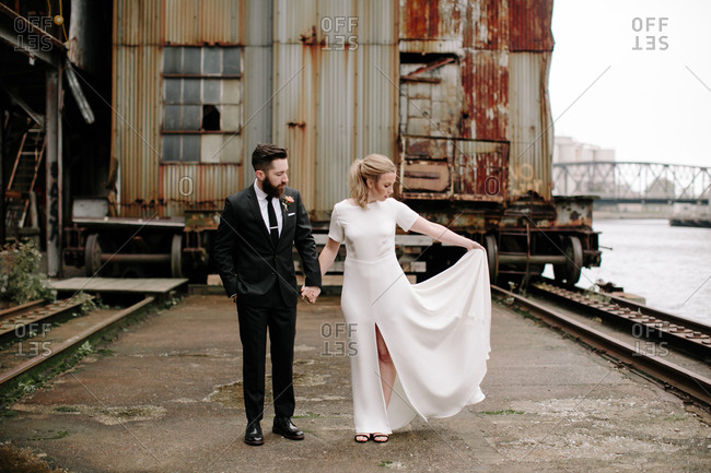 Bride holding her dress while walking hand in hand with groom through abandoned railroad yard
