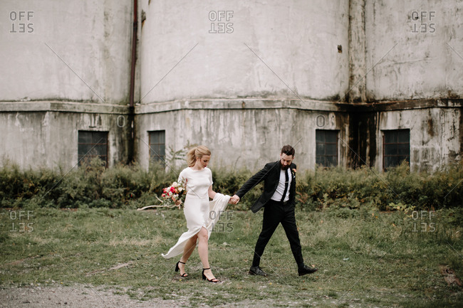 Bride and groom walking together through overgrown vegetation in front of abandoned buildings