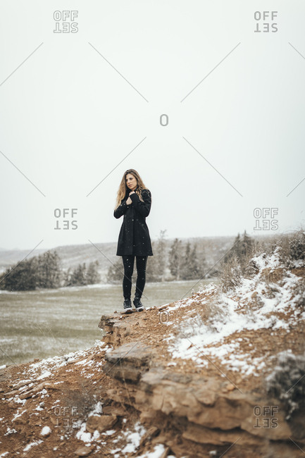 Cold blonde woman standing alone on desert cliff