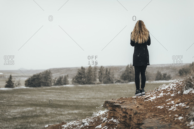 Back view of woman standing alone on scenic desert hill in winter