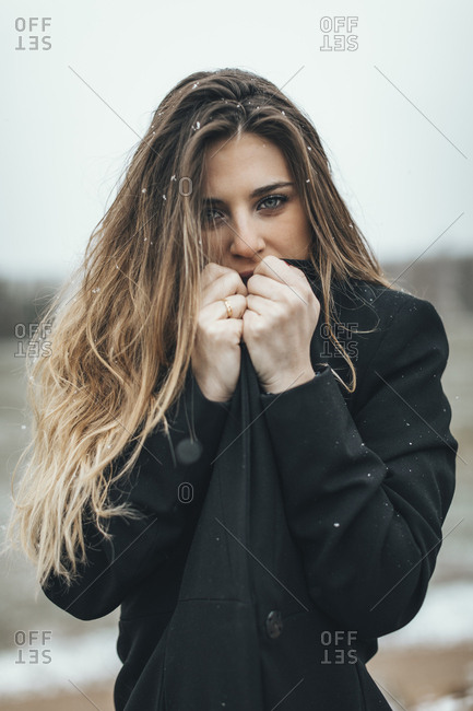 Female model pulling peacoat over chin in light snowfall