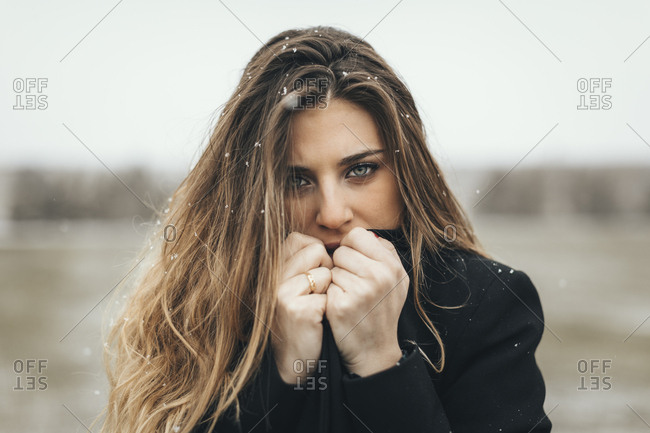 Cold woman clasping front of jacket in Lleida desert