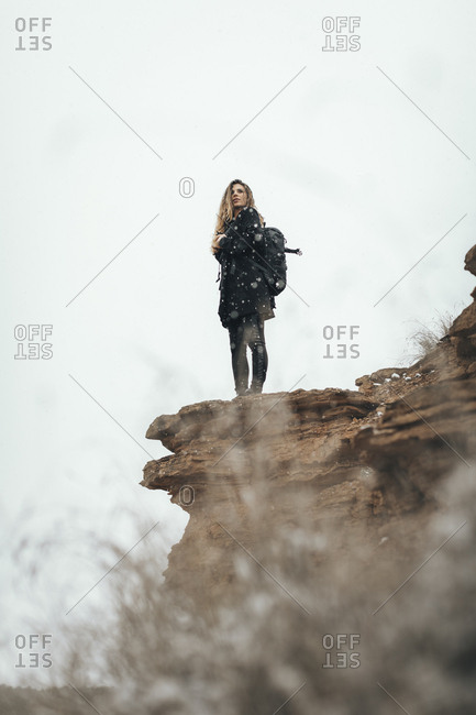 Lower angle view of Spanish woman in winter apparel backpacking in the desert