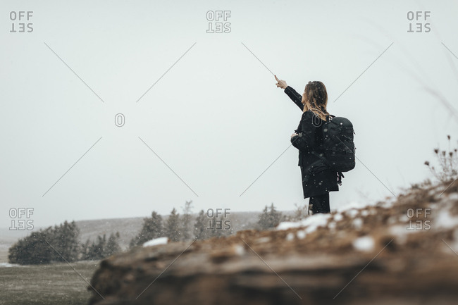 Woman hiking in Lledia, Spain pointing to sky