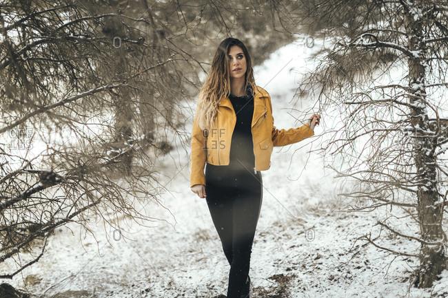 Female model walking alone in snowy woods