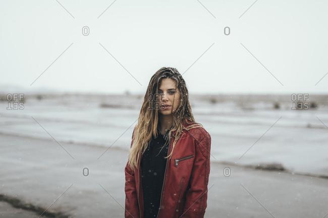 Woman in stylish winter jacket standing alone in dreary muddy field