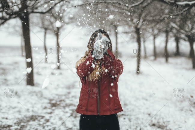 Woman clapping falling snow in secluded Lleida woods