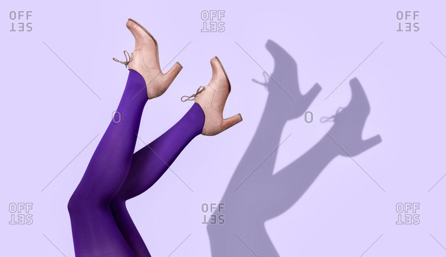 Legs of person wearing purple tights and high heel shoes