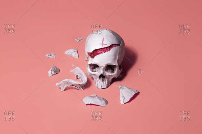 Broken skull with inverted cross and exposed brain