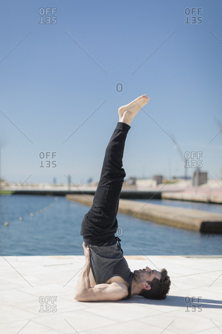 Man doing yoga posture outdoors in Barcelona, Spain