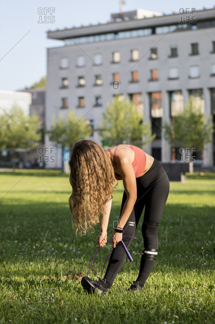 Young woman stretches with jump rope during an outdoor workout,