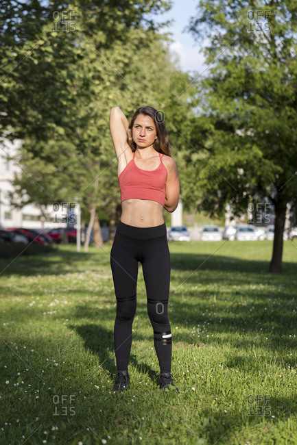 Young woman stretches her arms during an outdoor workout