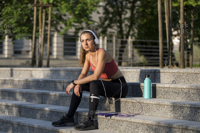 Young woman sits on stairs after a an outdoor workout